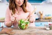 částečný pohled obézní ženy vaření čerstvý salát k večeři v kuchyni doma