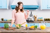 Photo cheerful overweight woman listening music in headphones at table with fresh vegetables in kitchen at home