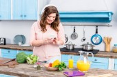 Photo smiling overweight woman in headphones using smartphone at table with fresh vegetables in kitchen at home