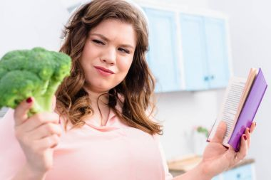 overweight woman in headphones with cookery book looking at fresh broccoli in hand in kitchen