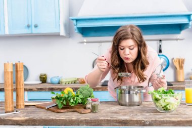 portrait of young overweight woman cooking soup in kitchen at home