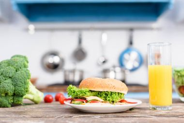 Close up view of burger on plate, fresh broccoli and glass of juice on wooden tabletop in kitchen stock vector