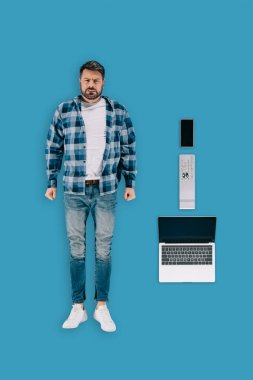 top view of stressed remote worker with smartphone, remote controller and laptop isolated on blue background