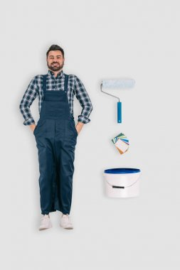 top view of repairman with paint roller and bucket of paint isolated on white background