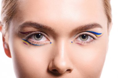 cropped image of woman with colored makeup with lines looking at camera isolated on white