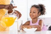 Photo african american mother pouring orange juice for daughter on kitchen