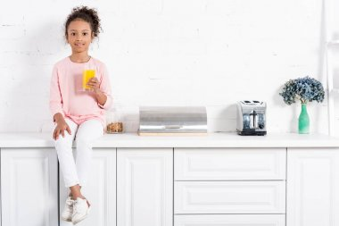 african american child with glass of orange juice sitting alone in kitchen