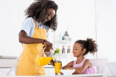 african american mother and daughter in aprons with orange juice on kitchen