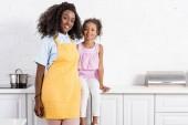 africká americká matka v zástěře a dcera pózuje na kuchyň