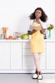 Fotografie promyšlené africká americká žena v zástěře drží kuchařka v kuchyni