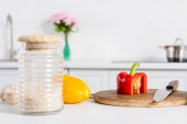 Photo rice in glass jar and bell peppers on wooden board with knife