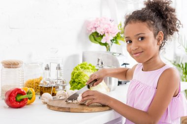 african american kid cutting vegetables on wooden board and looking at camera