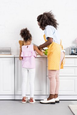 african american mother and daughter cutting vegetables on kitchen together