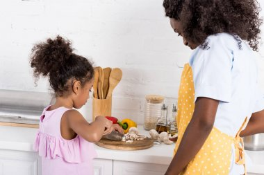 african american mom and daughter cutting vegetables on kitchen