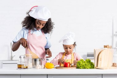 african american mother and daughter in chef hats cooking on kitchen