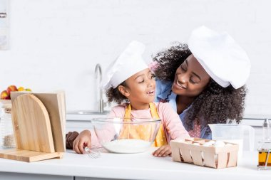 happy african american mother and daughter in chef hats making dough in bowl on kitchen