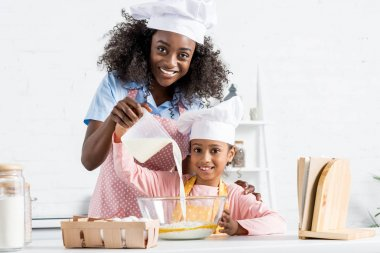 african american mother and daughter in chef hats pouring milk for dough on kitchen