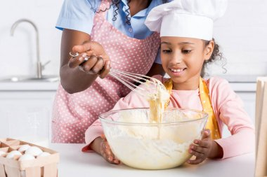 african american mother and daughter in chef hat making dough on kitchen