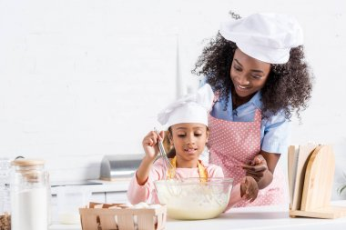 african american mother and daughter in chef hats mixing dough on kitchen with cookbook
