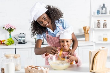 african american mother and daughter in chef hats mixing dough with whisk on kitchen