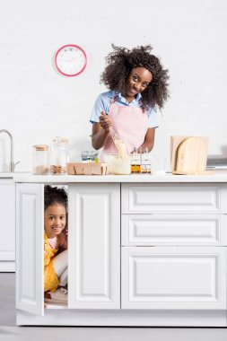 african american mother making dough while daughter hiding on kitchen
