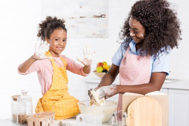 smiling african american mother and daughter kneading dough in bowl on kitchen