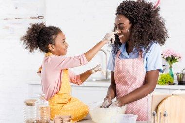 african american mother and daughter having fun while making dough on kitchen