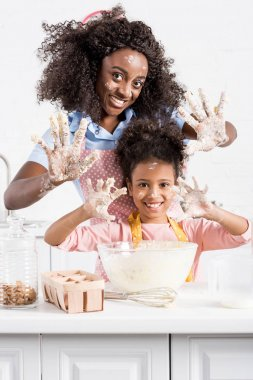 african american mother and funny daughter showing hands in dough on kitchen