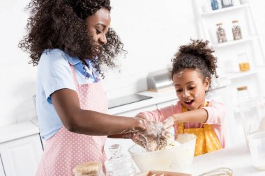 happy african american mother and daughter kneading dough on kitchen