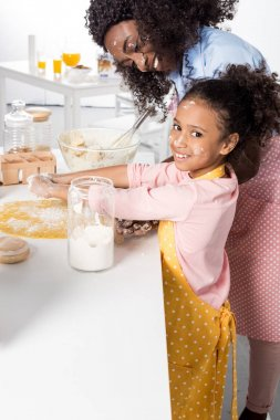 african american mother and smiling daughter kneading dough together on kitchen