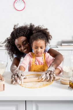 african american mother and daughter rolling dough with pin together on kitchen