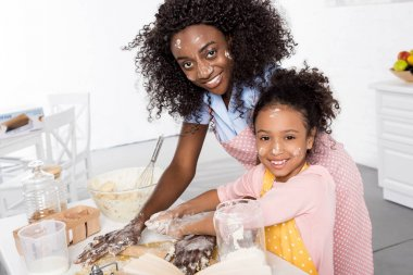 smiling african american mother and daughter kneading and rolling dough together on kitchen