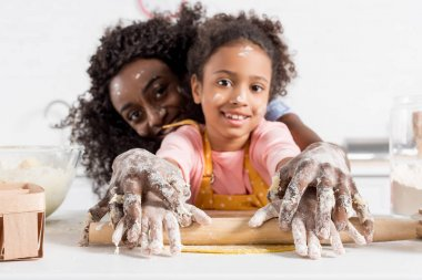 african american mother and smiling daughter rolling dough with rolling pin together on kitchen