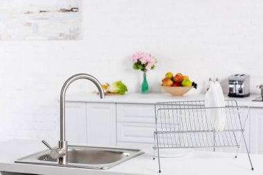 close up of sink and stand for dishes on kitchen