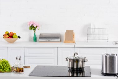 toaster and electric stove with saucepan on kitchen
