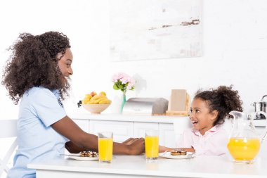 african american mother and daughter having pancakes and orange juice for breakfast in dining room