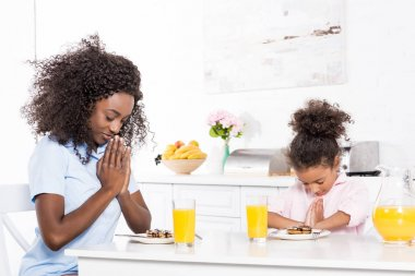 african american mother and daughter praying before breakfast in kitchen