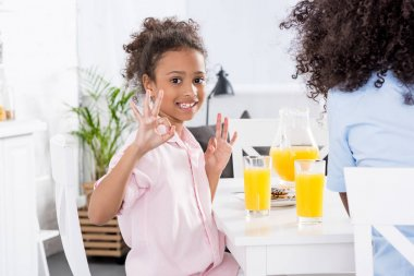 african american mother and daughter showing ok signs during breakfast in dining room