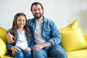 Šťastný otec a dcera sedí společně na žluté pohovce a usmívá se na kameru