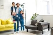 Šťastný otec se dvěma rozkošné děti se usmívá na kameru doma