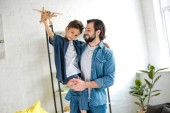 Photo happy father carrying cute little son playing with toy plane and looking at camera