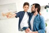 Fotografie glücklicher Vater mit entzückenden kleinen Sohn spielt mit Spielzeug Flugzeug und Blick in die Kamera zu Hause
