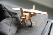 Photo close-up view of wooden toy plane model on couch