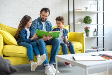 smiling father with children reading book together while sitting on sofa at home