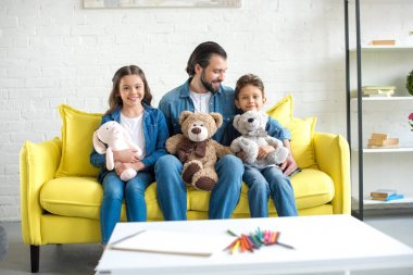 happy father with adorable little kids holding toys and sitting on sofa at home
