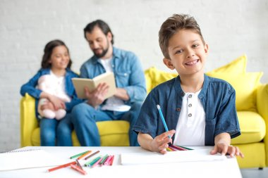 cute little boy drawing with colored pencils and smiling at camera while father and sister sitting on sofa behind