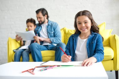 adorable child drawing with colored pencils and smiling at camera while father and brother sitting on sofa behind