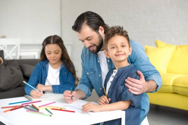 happy father and two adorable kids drawing with colored pencils at home