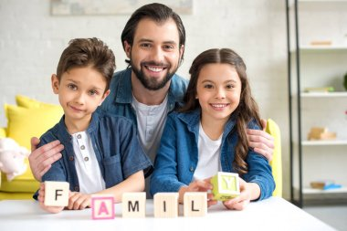 happy father with two children holding cubes with word family and smiling at camera