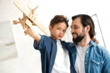 Close-up view of father and son playing with wooden toy plane stock vector